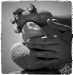 Des mains empilent des roches